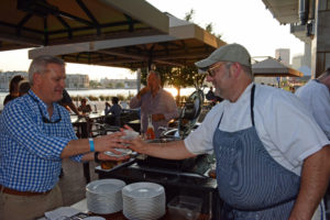 Chef Jerry Pellegrino serves up barbecue to one of the many hungry guests.