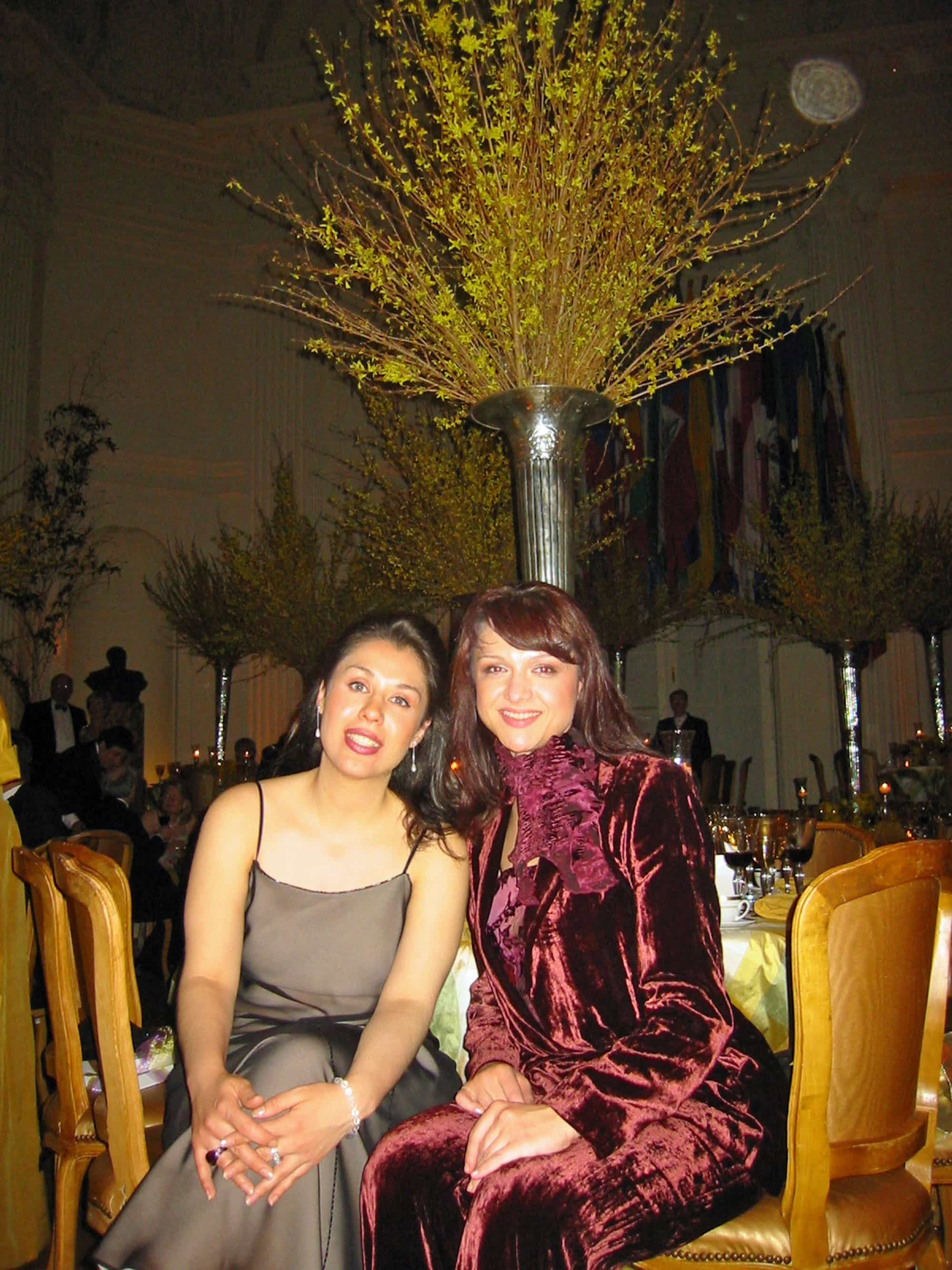 """Operatic sopranos Eugenia Garza and Tatiana Pavlovskaya also took a pared-down approach at their formal dinner. Garza is wearing a simple bronze sheath with spaghetti straps by Adrianna Pappell, while Pavlovskaya is channeling her inner '70s with a velvet burgundy pantsuit by – """"I can't remember!"""" she said. But, it looks very vintage Yves St. Laurent to me."""
